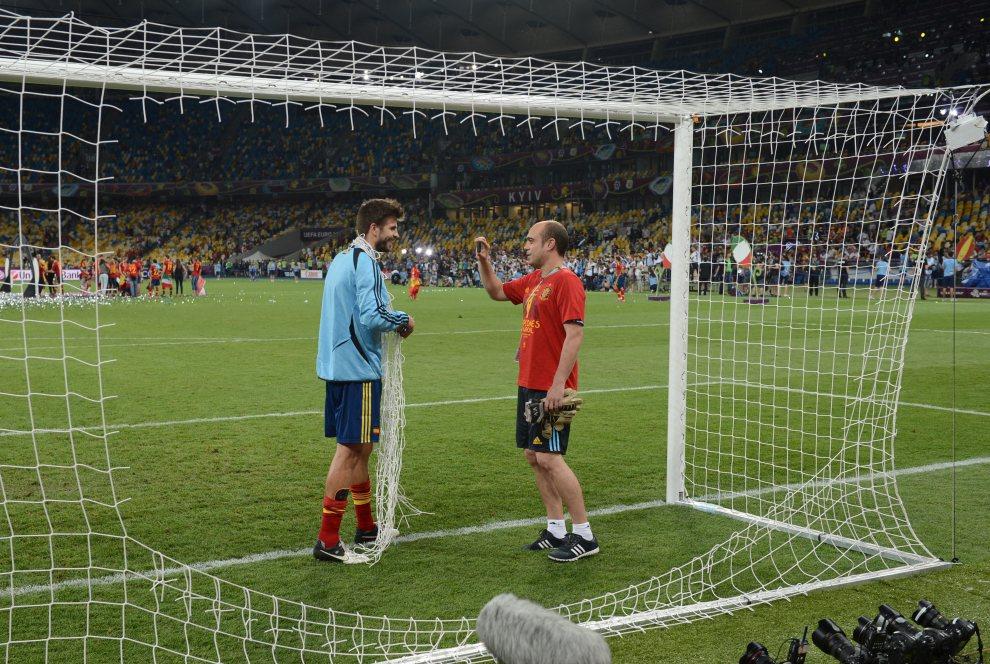 39.UKRAINA, Kijów, 1 lipca 2012: Gerard Pique (Hiszpania) wycina na pamiątkę siatkę z bramki po zdobytym mistrzostwie. AFP PHOTO / DAMIEN MEYER