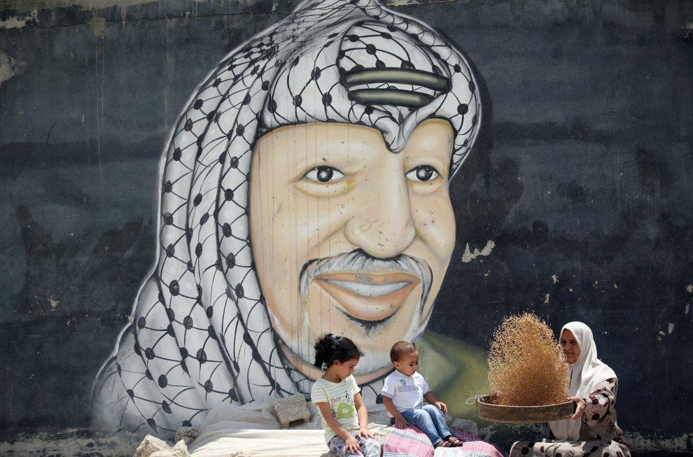 3.AUTONOMIA PALESTYŃSKA, Dżalama, 5 lipca 2012: Kobieta odsiewa ziarno od plew na tle muralu z wizerunkiem Jasera Arafata. AFP PHOTO   / SAIF DAHLAH