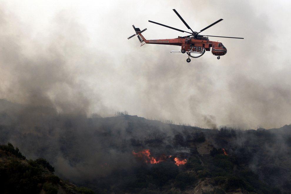 3.GRECJA, Patras, 18 lipca 2012: Helikopter straży pożarnej rozpryskuje wodę na obszarem zagrożonym przez ogień. AFP PHOTO/ Angelos Tzortzinis