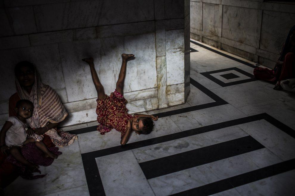 3.INDIE, New Delhi, 1 czerwca 2012: Dziewczynka przeciąga się na chłodnej, marmurowej posadzce. (Foto: Daniel Berehulak /Getty Images )