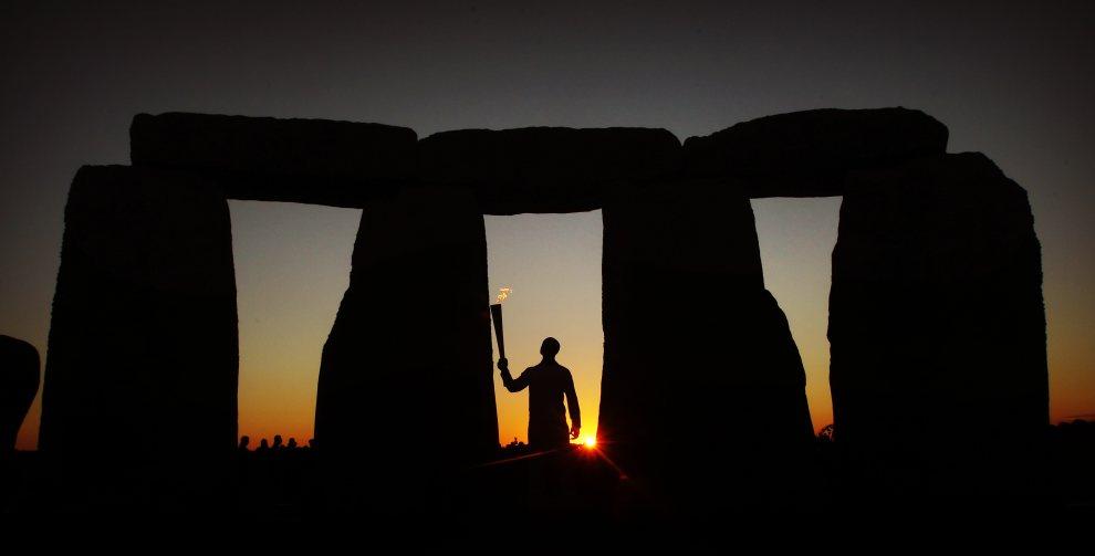 3.WIELKA BRYTANIA, Stonehenge, 12 lipca 2012: Sprinter Michael Johnson trzyma zapaloną pochodnię na tle  Stonehenge. (Foto: LOCOG via Getty Images)