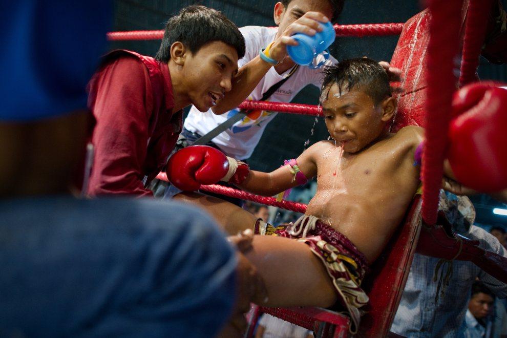 41.TAJLANDIA, Buriram, 28 czerwca 2012: Młody zawodnik muay thai odpoczywa w trakcie wlaki na ringu w Buriram. AFP PHOTO / Nicolas ASFOURI