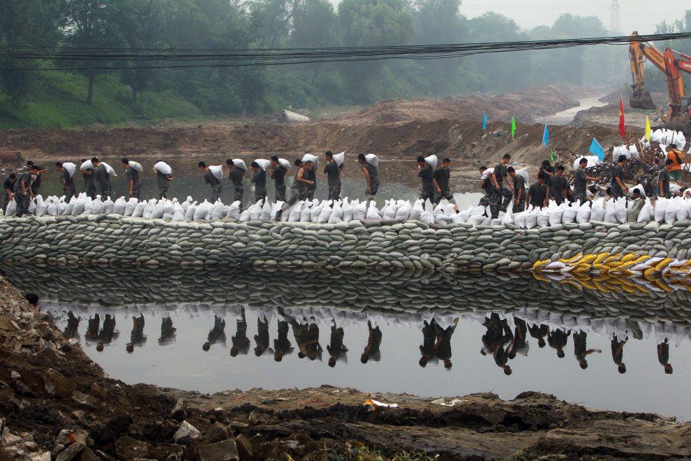 4.CHINY, Pekin, 26 lipca 2012: Układanie worków z piaskiem na brzegu wzbierającej rzeki. AFP PHOTO