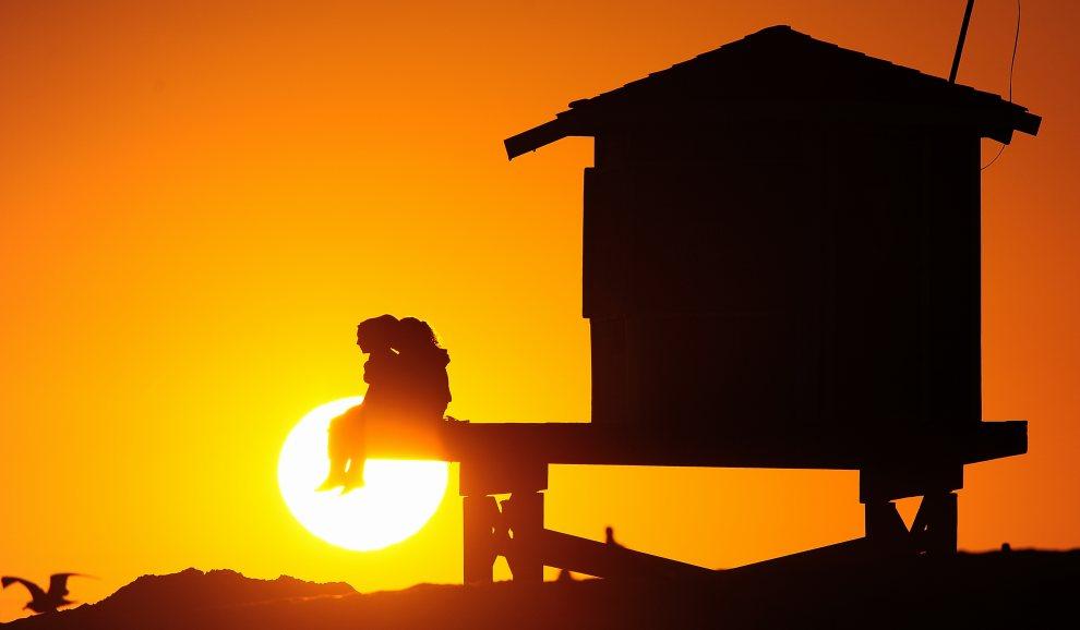 5.USA, Seal Beach, 9 lipca 2012: Budka ratowników i odpoczywający na niej ludzi, na tle zachodzącego słońca. AFP PHOTO / Frederic J. BROWN