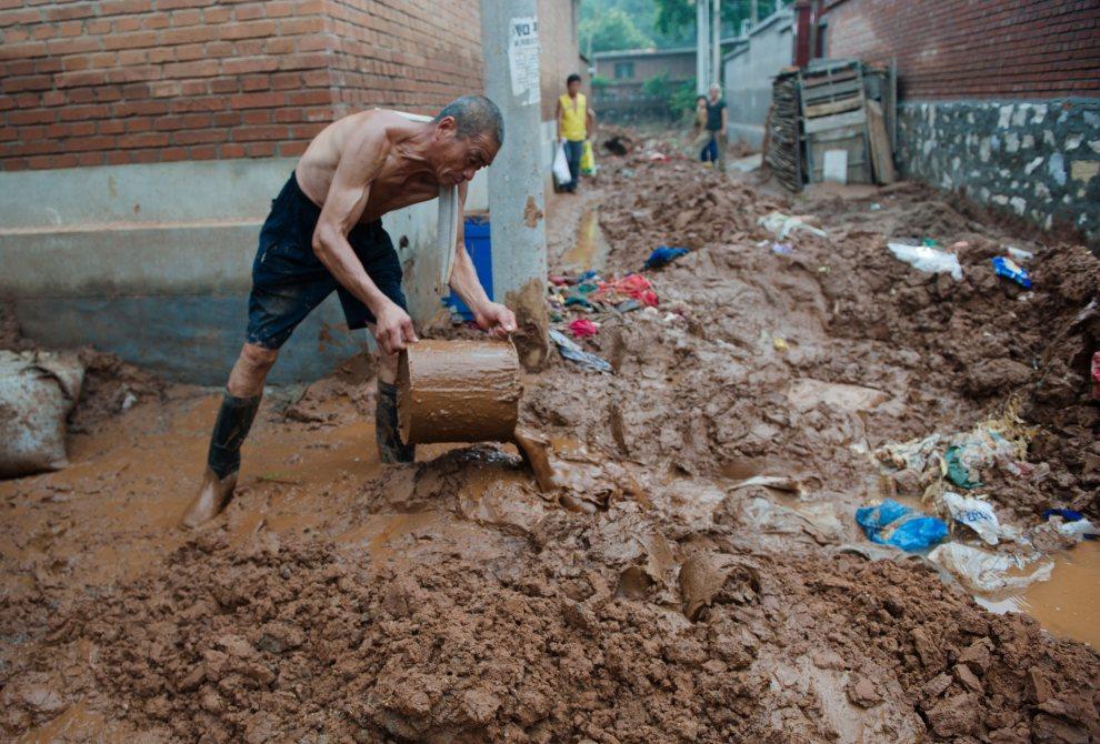 5.CHINY, Pekin, 26 lipca 2012: Mężczyzna wybiera z domu błoto naniesione w wyniku ulewnego deszczu. AFP PHOTO