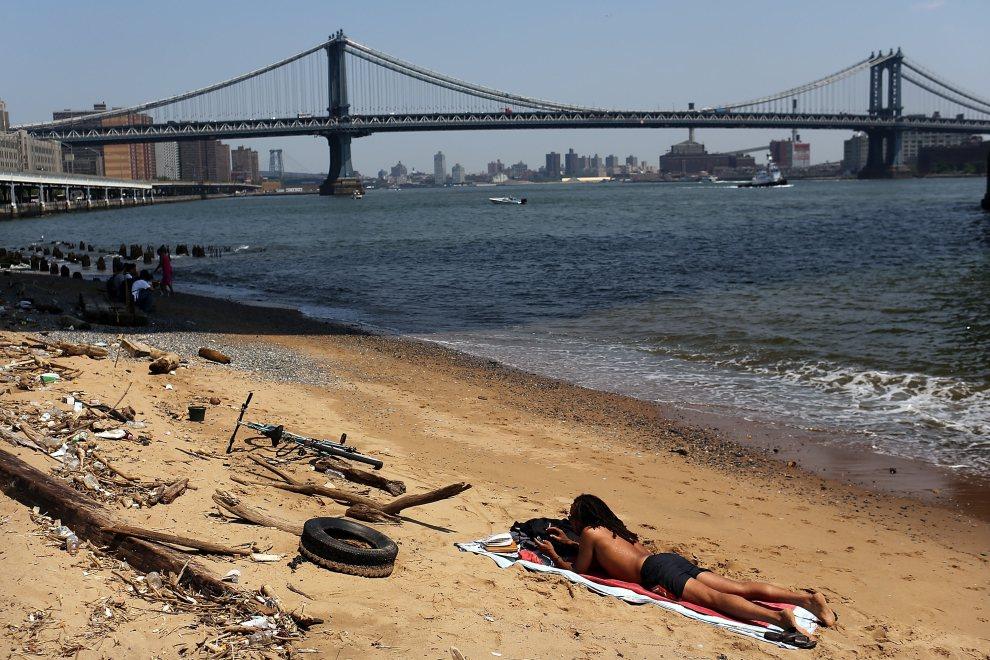 5.USA, Nowy Jork, 21 czerwca 2012: Mężczyzna odpoczywa na małej plaży nad East River. (Foto: Spencer Platt/Getty Images)
