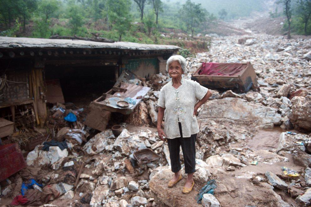 6. CHINY, Pekin, 26 lipca 2012: Starsza kobieta pośród pozostałości swojego domu. AFP PHOTO