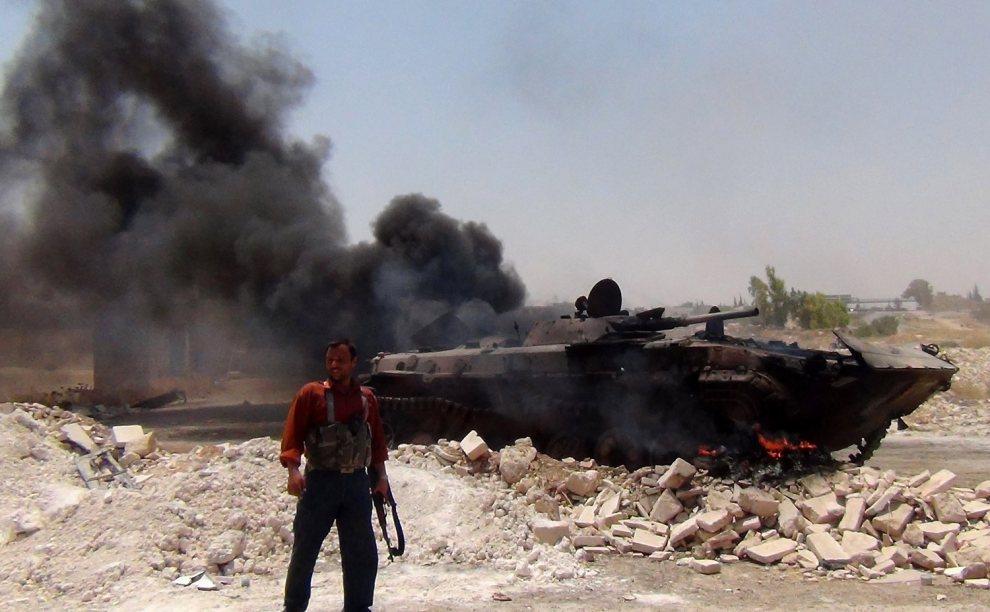 6.SYRIA, Jarjanaz, 9 lipca 2012:  Rebeliant obok zniszczonego pojazdu. AFP PHOTO/HO/SHAAM NEWS NETWORK