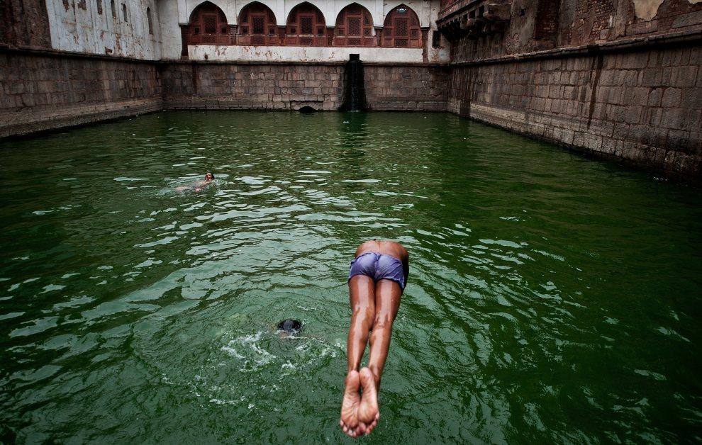 7.INDIE, New Delhi, 10 maja 2012: Chłopiec skacze do wody studni w Nizamuddin Dargah. AFP PHOTO/ MANAN VATSYAYANA
