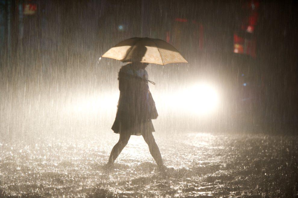 7.CHINY, Pekin, 21 lipca 2012: Kobieta idzie ulicą w trakcie ulewnego deszczu. AFP PHOTO / Ed Jones