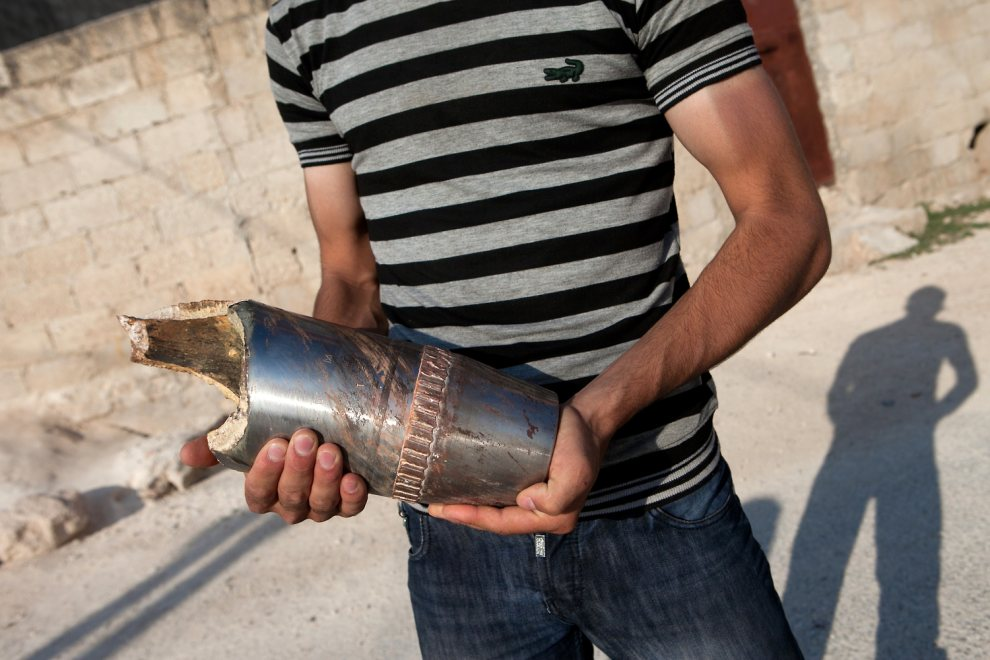 7.SYRIA, Khan Sheikhun, 8 lipca 2012: Syryjczyk z fragmentem pocisku artyleryjskiego. AFP PHOTO/LO