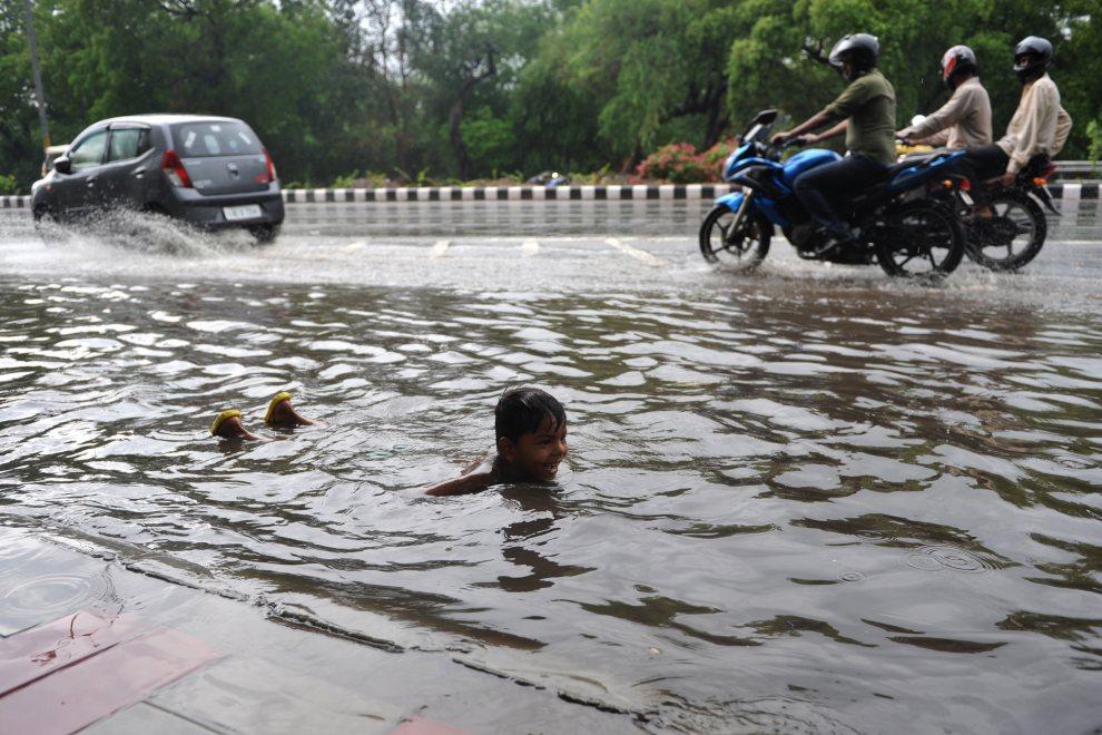 9.INDIE, New Delhi, 12 lipca 2012: Dziecko bawi się na ulicy po przejściu monsunu. AFP PHOTO/SAJJAD HUSSAIN