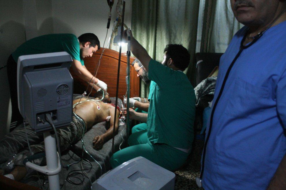 9.SYRIA, Al-Kusajr, 10 lipca 2012: Lekarze udzielają pomocy rannemu rebeliantowi. AFP PHOTO/ANTONIO PAMPLIEGA