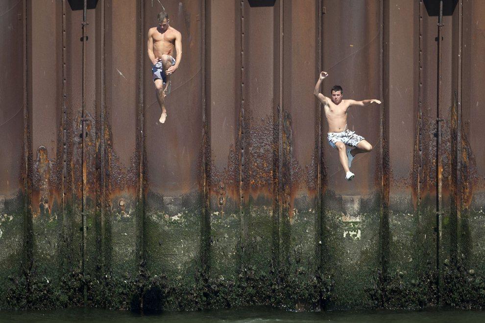 9.HOLADNIA, Haga, 25 lipca 2012: Nastolatkowie skaczą do wody w porcie Scheveningen. AFP PHOTO / ANP / EVERT-JAN DANIELS