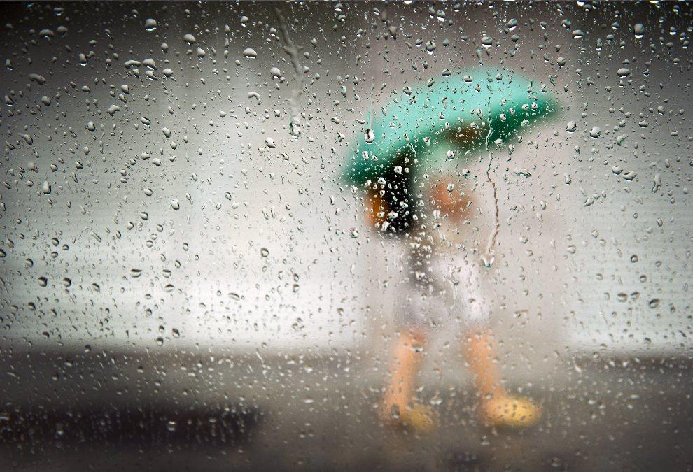 10.NIEMCY, Monachium, 6 sierpnia 2012: Kobieta z parasolem widziana przez mokrą od deszczu szybę. AFP PHOTO / VICTORIA BONN-MEUSER
