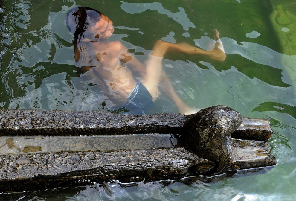 10.NEPAL, Lalitpur, 20 sierpnia 2012: Chłopiec pływa z zbiorniku, gdzie zbierana jest woda. AFP PHOTO/ Prakash MATHEMA