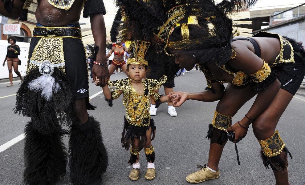 10.WIELKA BRYTANIA, Londyn, 26 sierpnia 2012: Mała uczestniczka parady w towarzystwie rodziców. EPA/FACUNDO ARRIZABALAGA