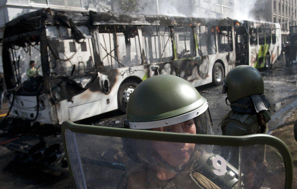 13.CHILE, Santiago, 8 sierpnia 2012: Policjanci na tle spalonego przez protestujących studentów autobusu. AFP PHOTO/Claudio SANTANA