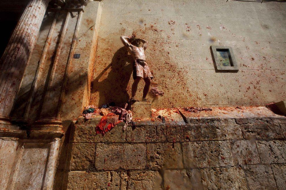 14.HISZPANIA, Bunol, 29 sierpnia 2012: Uczestnik Tomatiny rzuca pomidorami w zebranych ludzi. AFP PHOTO / BIEL ALINO