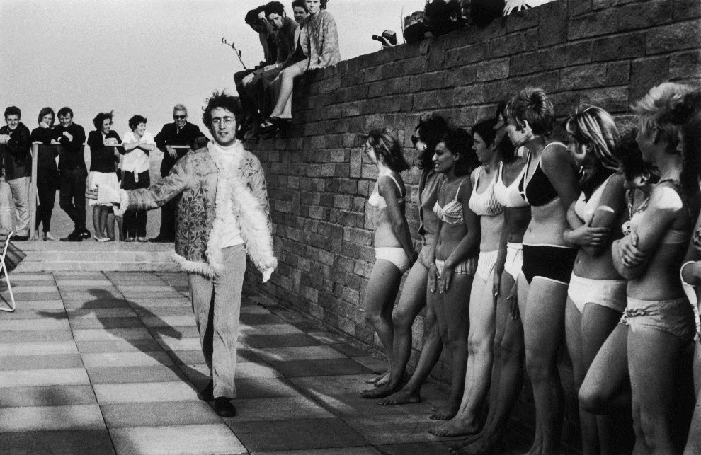 "16.	WIELKA BRYTANIA, Newquay, 14 września 1967: John Lennon mija dziewczyny występujące w filmie ""The Magical Mystery Tour"". (Foto: Jim Gray/Keystone/Getty Images)"