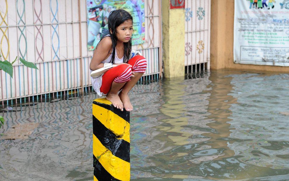 17.FILIPINY, Manila, 8 sierpnia 2012: Przemoknięta dziewczynka chroni się przed wodą na zalanej ulicy w Manili. AFP PHOTO / Jay DIRECTO