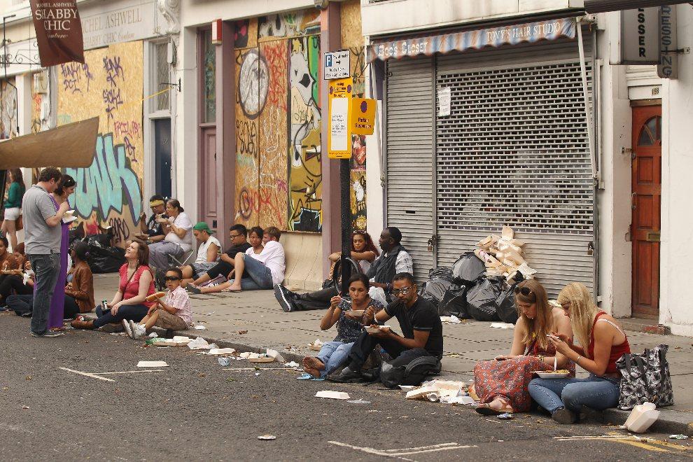 17.WIELKA BRYTANIA, Londyn, 26 sierpnia 2012: Uczestnicy zabawy w Notting Hill podczas posiłku. (Foto: Oli Scarff/Getty Images)