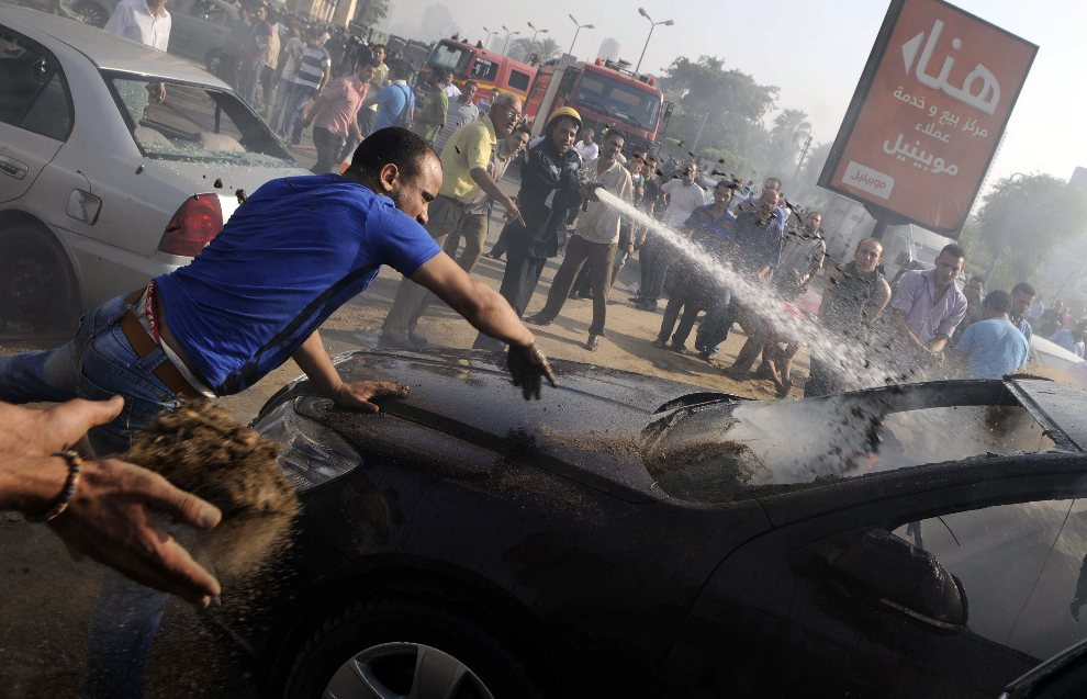 18.EGIPT, Kair, 2 sierpnia 2012: Strażacy i przechodnie gaszą samochód podpalony w czasie zamieszek. AFP PHOTO/MOHAMED HOSSAM