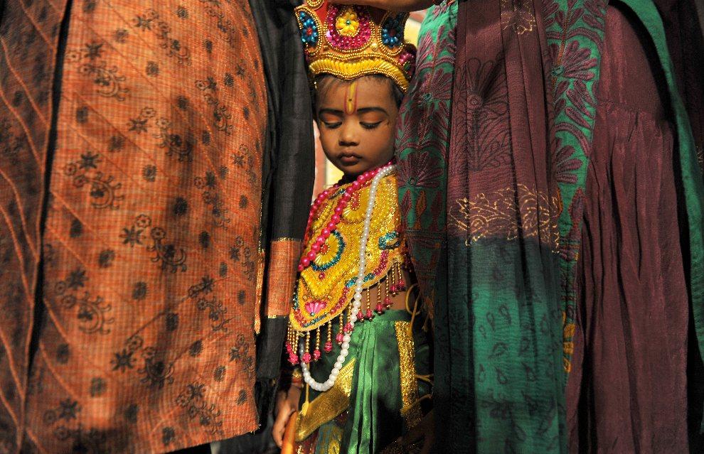 19.INDIE, Bangalore, 9 sierpnia 2012: Dziecko przebrane za Krysznę w otoczeniu rodziny. AFP PHOTO/ Manjunath KIRAN
