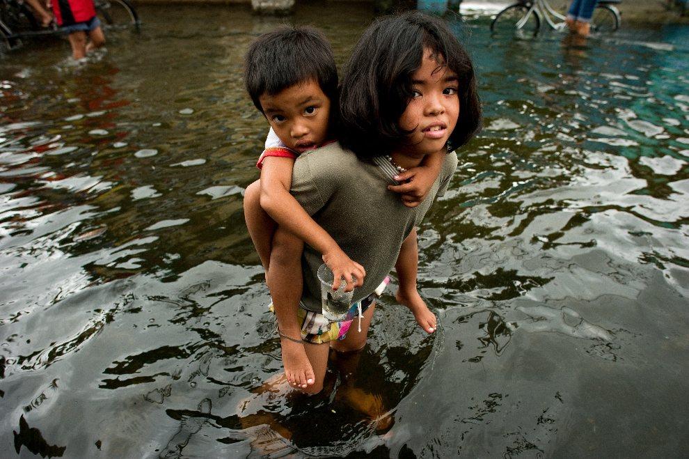 21.FILIPINY, Valenzuela, 13 sierpnia 20120: Dziewczynka przenosi dziecko przez zalaną ulicę. AFP PHOTO / Nicolas ASFOURI