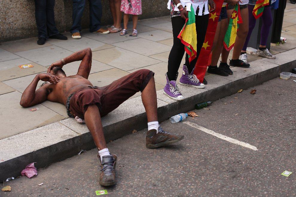 21.WIELKA BRYTANIA, Londyn, 26 sierpnia 2012: Mężczyzna leżący na ulicy wśród uczestników zabawy. (Foto: Oli Scarff/Getty Images)
