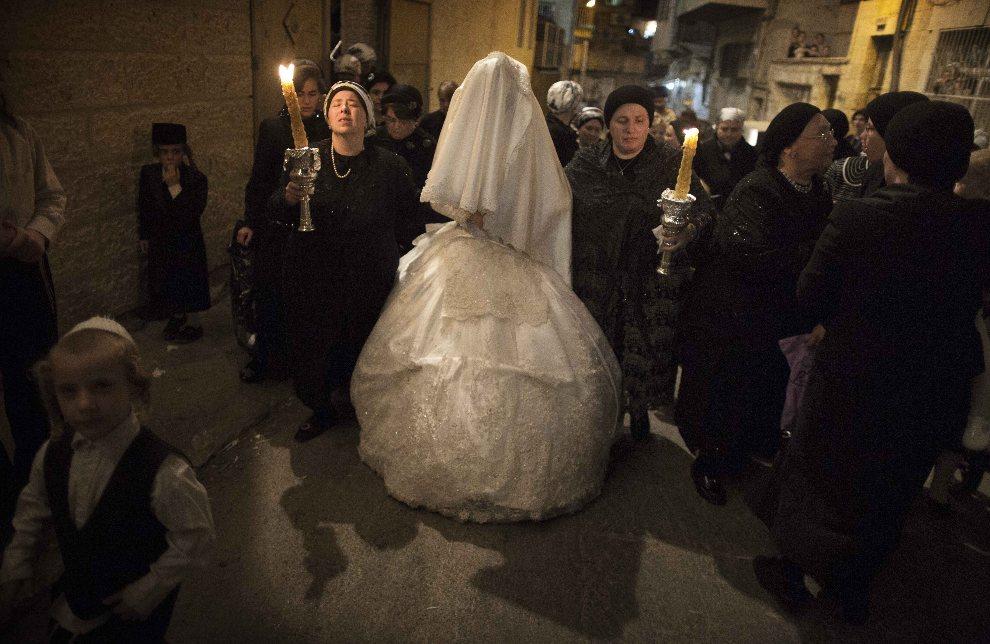 22.IZRAEL, Jerozolima, 28 sierpnia 2012: Kobiety prowadzą pannę młodą na ceremonię zaślubin. AFP PHOTO/MENAHEM KAHANA