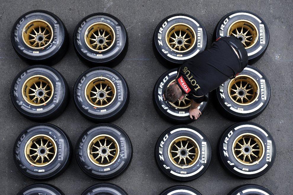 25.BELGIA, Spa, 30 sierpnia 2012: Mechanik zespołu Lotus sprawdza opony przed rozpoczęciem  Grand Prix Belgii. AFP PHOTO / JOHN THYS