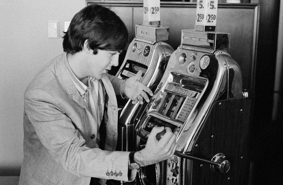27.	USA, Las Vegas, 20 sierpnia 1964: Paul McCartney gra na automacie w Las Vegas. (Foto: Harry Benson/Daily Express/Hulton Archive/Getty Images)