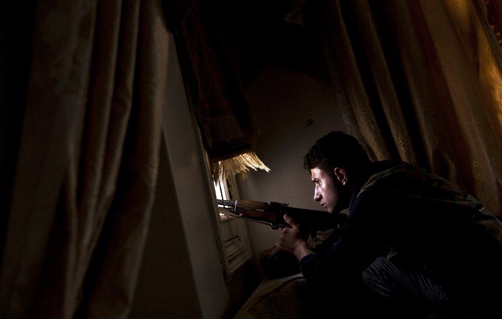 28.SYRIA, Aleppo, 14 sierpnia 2012: Rebeliant wypatruje pozycji oddziałów rządowych. AFP PHOTO / ACHILLEAS ZAVALLIS