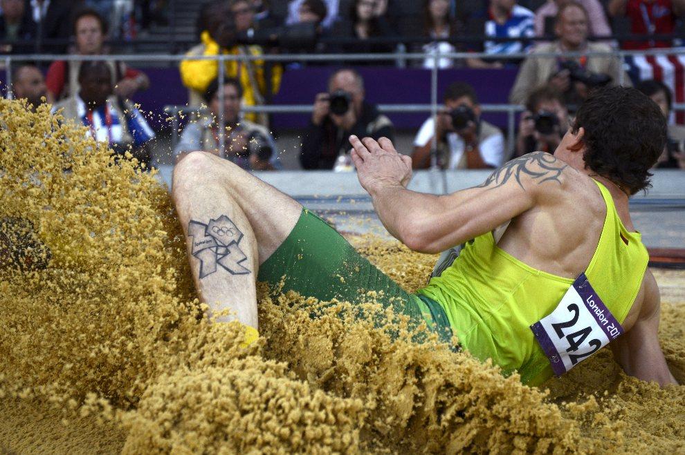 30.WIELKA BRYTANIA, Londyn, 3 sierpnia 2012: Povilas Mykolaitis ląduje w piasku po oddanym skoku. AFP PHOTO / ADRIAN DENNIS