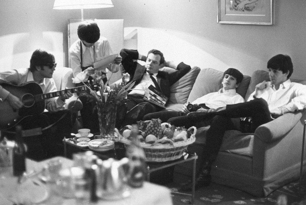33.FRANCJA, Paryż, 16 czerwca 1964: John Lennon gra w pokoju hotelowym w towarzystwie managera, Briana Epstein'a i reszty zespołu. (Foto: Harry Benson/Getty   Images)