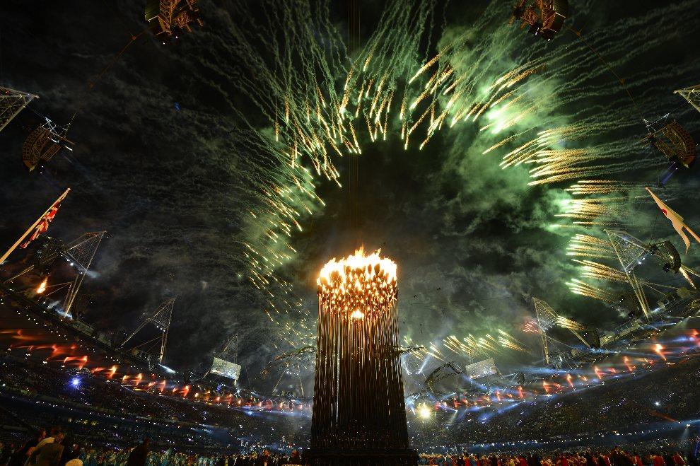 34.WIELKA BRYTANIA, Londyn, 29 sierpnia 2012: Sztuczne ognie rozświetlają niebo nad płonącym zniczem olimpijskim. AFP PHOTO / LEON NEAL