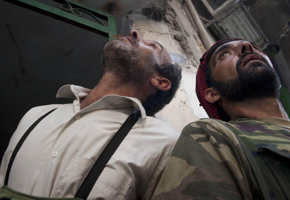 4.SYRIA, Aleppo, 23 sierpnia 2012: Rebelianci chronią się przed ostrzałem ze śmigłowca. AFP PHOTO / JAMES LAWLER DUGGAN