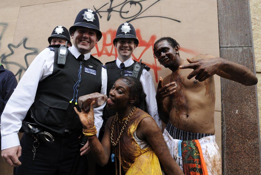 4.WIELKA BRYTANIA, Londyn, 28 sierpnia 2011: Uczestnicy parady, ubrudzeni czekoladą, pozują do zdjęcia z policjantami. AFP PHOTO/ FACUNDO ARRIZABALAGA