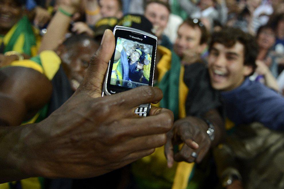5.WIELKA BRYTANIA, Londyn, 11 sierpnia 2012: Usain Bolt robi sobie zdjęcie z kibicami. AFP PHOTO / ADRIAN DENNIS