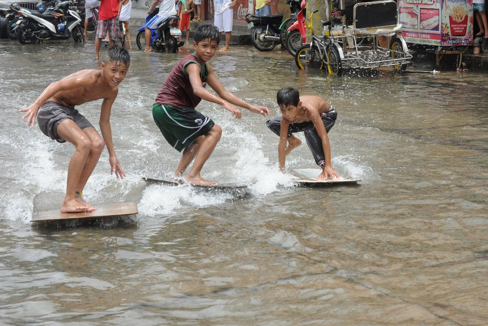 5.FILIPINY, Manila, 2 sierpnia 2012: Chłopcy bawią się na zalanej wodą ulicy. AFP PHOTO / JAY DIRECTO