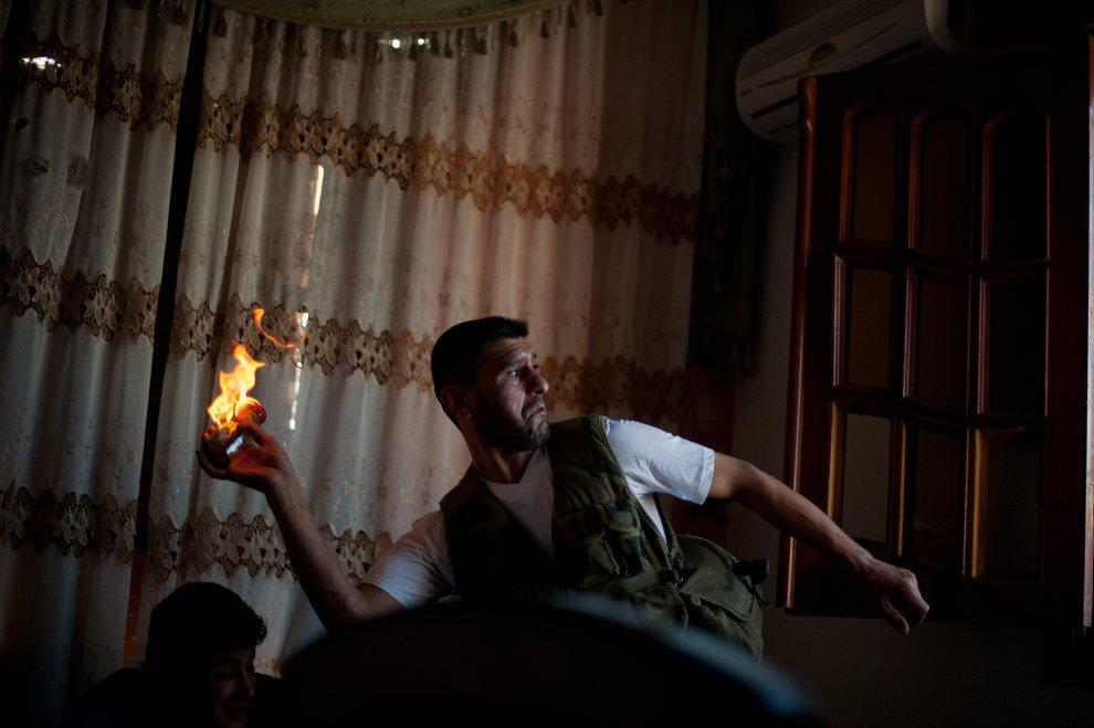 5.SYRIA, Aleppo, 29 sierpnia 2012: Rebeliant rzuca butelkę z koktajlem Mołotowa.  AFP PHOTO / ZAC BAILLIE BAILLIE