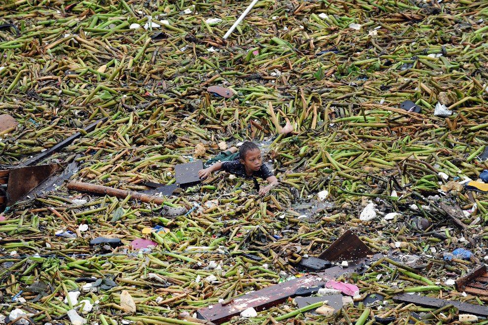 6.FILIPINY, Manila, 20 lipca 2012: Chłopiec wyławiający przedmioty niesione przez wezbraną wodę. AFP PHOTO / TED ALJIBE