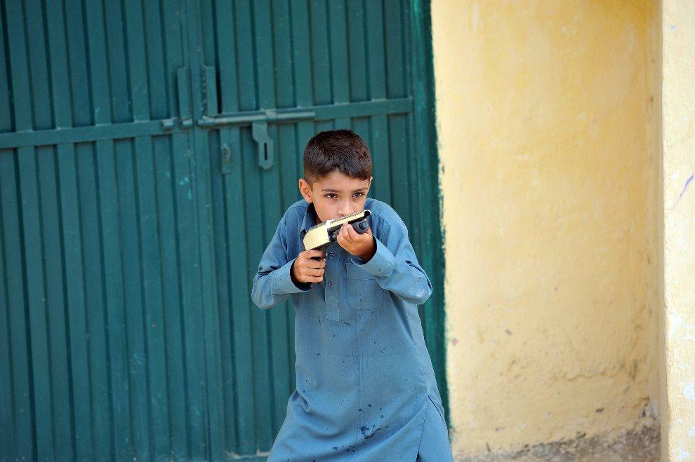 7.PAKISTAN, Islamabad, 20 sierpnia 2012: Chłpak z zabawkową bronią w pobliżu domu dziewczynki Rimshy Masih. Rimsha, chora na zespół Downa, została oskarżona o spalenie stron Koranu. AFP PHOTO / AAMIR QURESHI