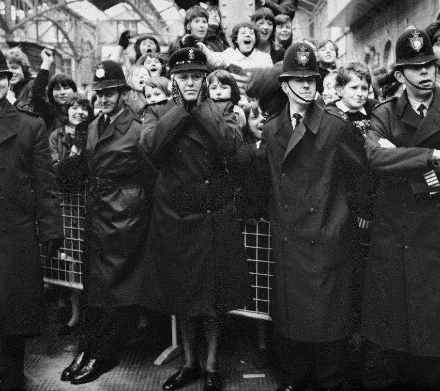 8.WIELKA BRYTANIA, Londyn, 6 kwietnia 1964: Policjantka zakrywająca uszy w otoczeniu fanów zespołu. (Foto: Daily Express/Archive Photos/Getty Images)