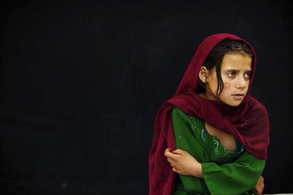 9.AFGANISTAN, Kabul, 27 sierpnia 2012: Dziewczynka przygląda się trenującym żonglerom. AFP PHOTO/ Jose CABEZAS