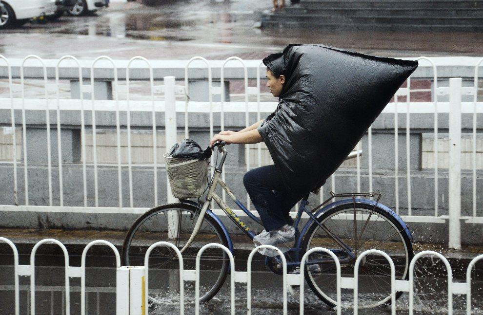 10.CHINY, Pekin, 1 września 2012: Kobieta na rowerze w deszczowy dzień. AFP PHOTO/WANG ZHAO