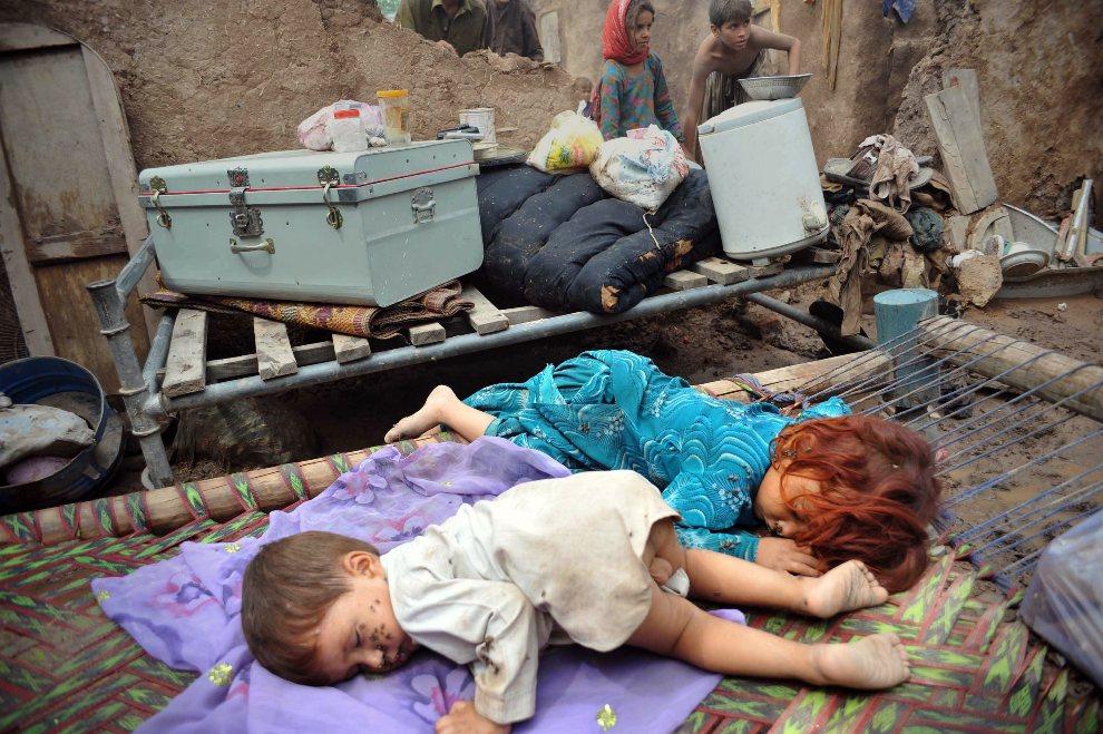 12.PAKISTAN, Peszawar, 6 września 2012: Dzieci śpiące przed domem zniszczonym przez powódź. AFP PHOTO/A MAJEED