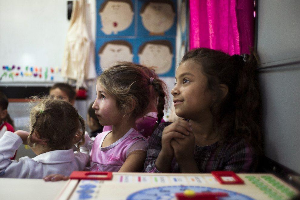 14.FRANCJA, Le Bourget, 6 września 2012: Romskie dzieci mieszkające w podmiejskim obozie, podczas zajęć szkolnych zorganizowanych w autobusie. AFP PHOTO / FRED   DUFOUR
