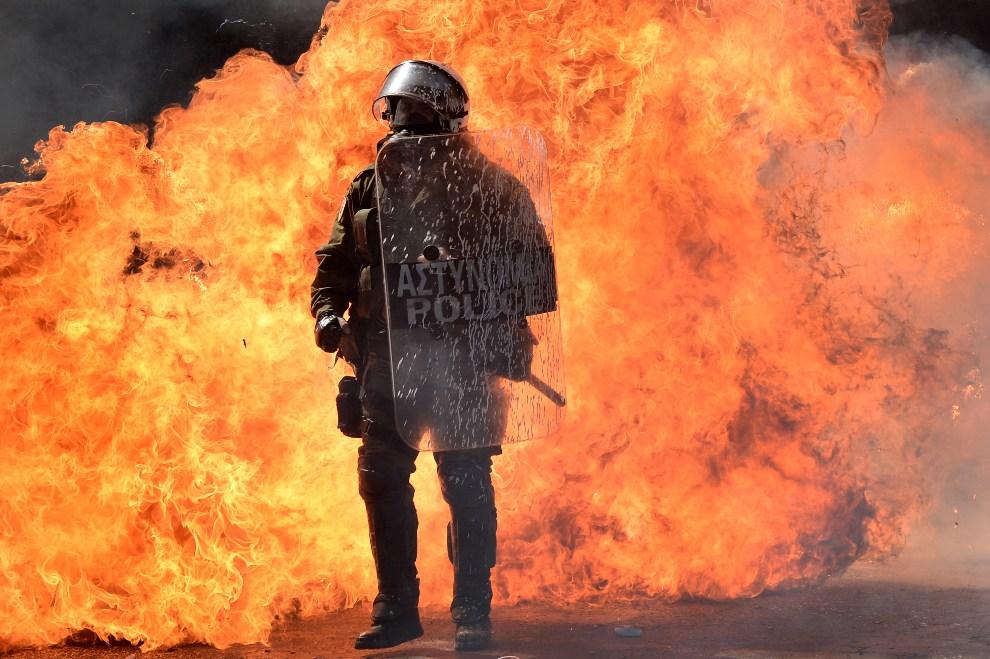 16.GRECJA, Ateny, 26 września 2012: Policjant na tle płomieni z rzucanych koktajli Mołotowa. AFP PHOTO / ARIS MESSINIS